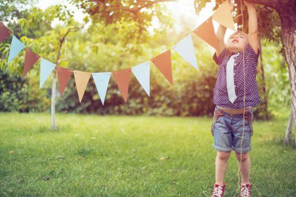 Enfant qui accroche une banderole dans un arbre